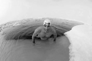 British explorer and endurance swimmer Lewis Gordon Pugh is half immersed in the sea at the North Pole July 15, 2007. Pugh swam one kilometre in 18 minutes and 50 seconds in temperatures of minus 1.8 degrees centigrade, wearing only briefs, cap and goggles, the organisers said. Picture taken July 15, 2007. REUTERS/Handout. EDITORIAL USE ONLY. NOT FOR SALE FOR MARKETING OR ADVERTISING CAMPAIGNS. - RTR1RX9F